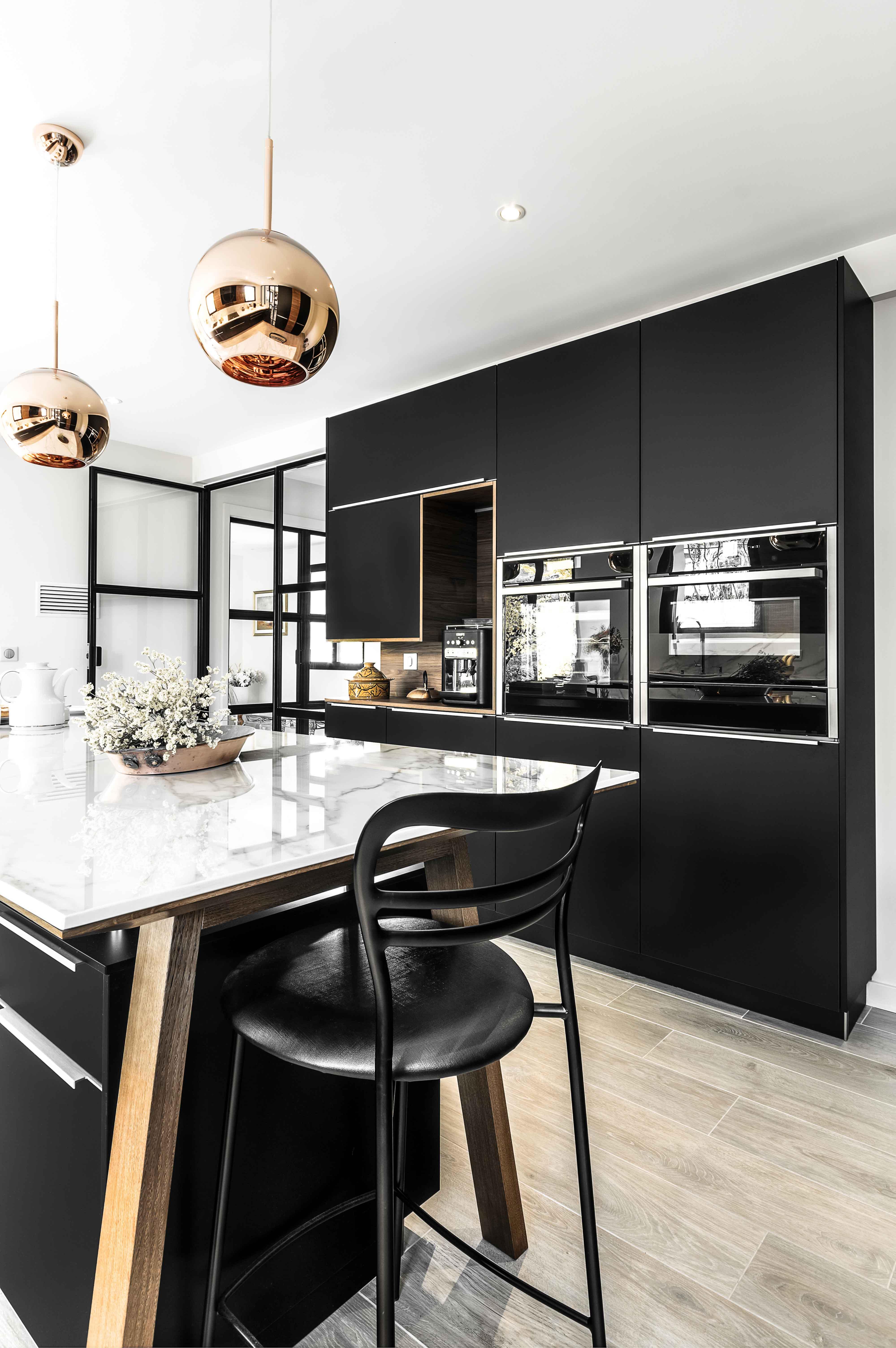 alliance du bois du marbre et du noir pour une cuisine aux influences modernes et nordiques