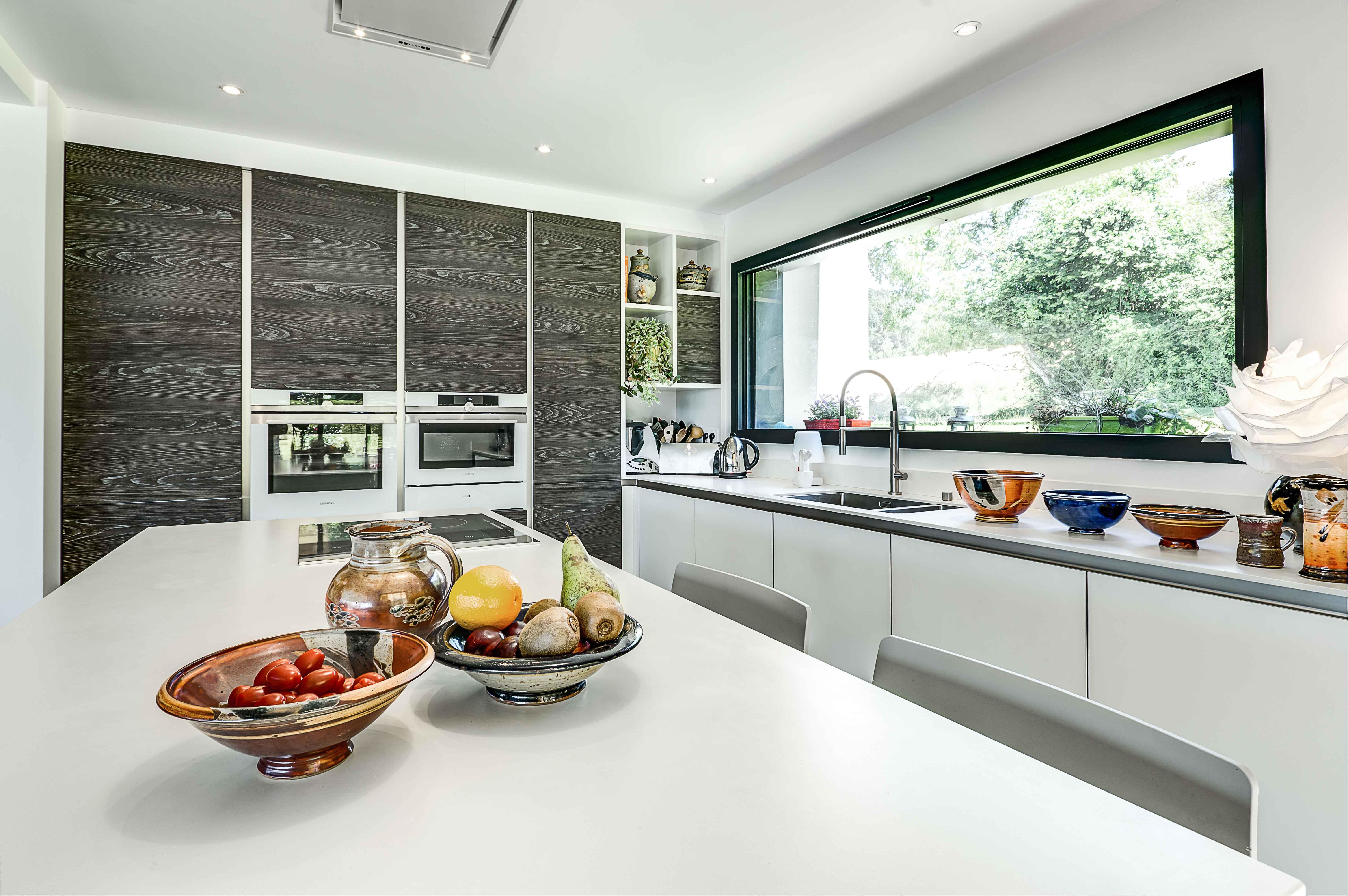 cuisine vue îlot central avec intégration électroménager haut de gamme design contemporain blanc nacré et imitation bois