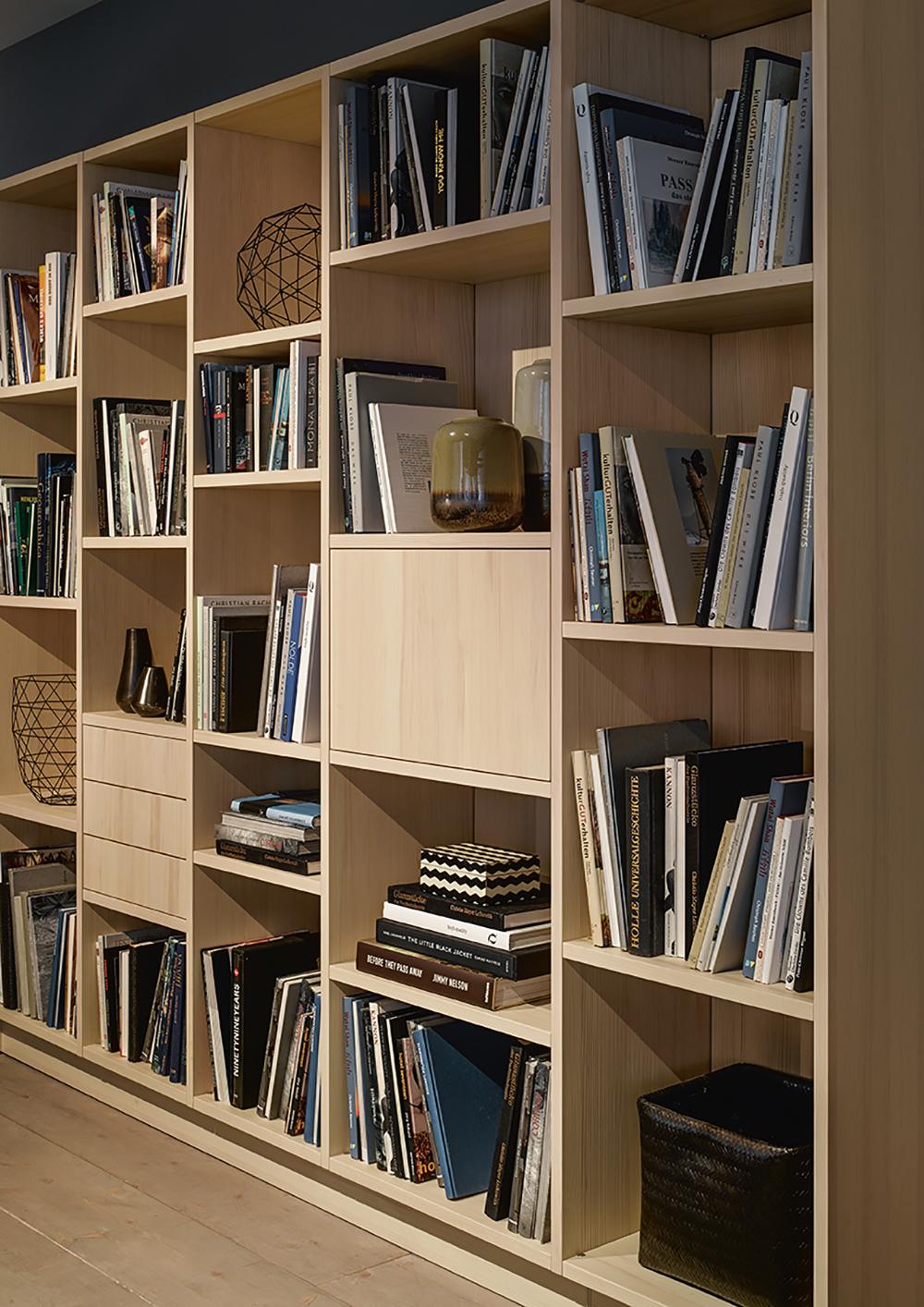 Bibliothèque style bois avec multiples rangements livres décorations bougeoirs