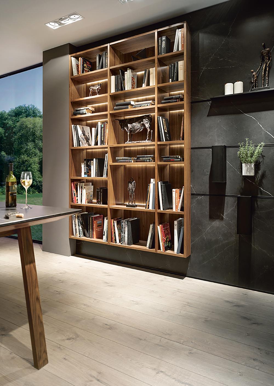 Espace de rangement style moderne en bois intégré en décoration à côté d'une cuisne en marbre noir moderne et chic